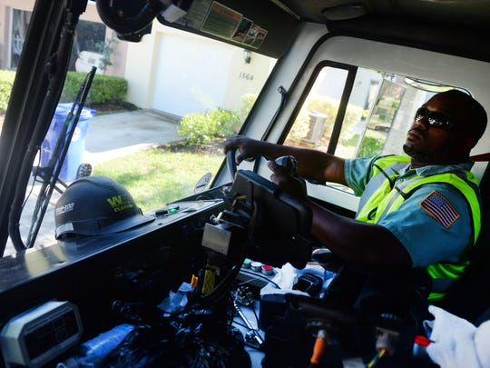 Demetrius Houston, a residential driver and 10-year veteran with Waste Management, makes his way through the Pointe West neighborhood of Vero Beach, Wednesday, Sept. 28, 2016, emptying trash carts left at the end of driveways. One year ago, Waste Management began a new collection system for both household trash and recyclable materials. The recycling system is a single-stream system which does not require customers to sort materials.