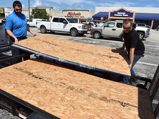 Oct 4, 2016; Vero Beach, FL, USA; Ryan Hartmann, left, helps Travis Purvis load wood into a trailer in the parking lot of Lowe's in Vero Beach in preparation for the arrival of Hurricane Matthew. Mandatory Credit: Patrick Dove/Treasure Coast News via USA TODAY NETWORK