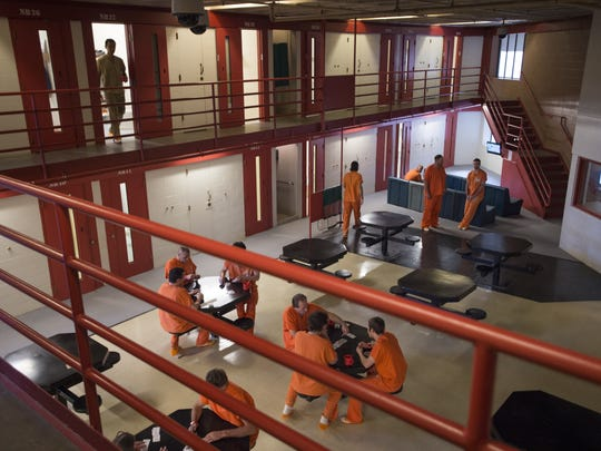 Inmates move around a housing area at Larimer County