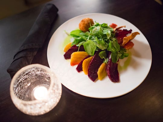 A beet salad is served with watercress and a lemon