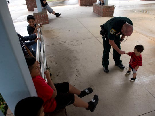 Martin County Sheriff's Deputy Tommy Smith high fives Manuel Paz Reckons, 1, of Stuart, as Hurricane Matthew approaches on Oct. 6, 2016 at the American Red Cross shelter at Hidden Oaks Middle School in Palm City. About 175 people stayed at the shelter throughout the storm.