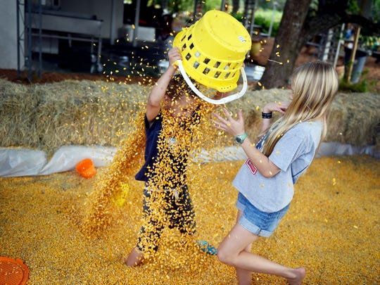 Peter Holihen, 5, (left) pours corn kernels over his