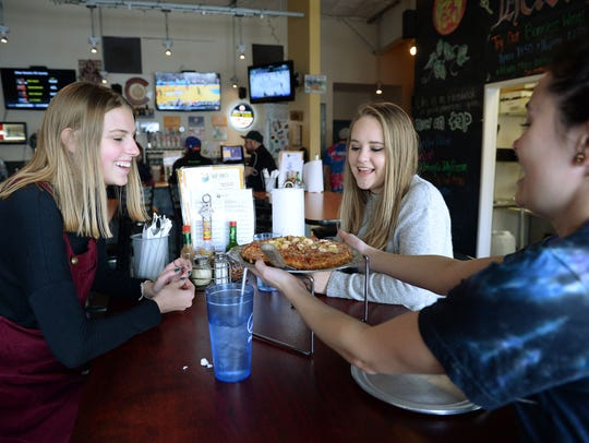 Jessica Croft serves pizza to Jane Fleetwood, left,