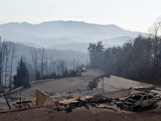 A burned out car rests outside a destroyed home Tuesday,
