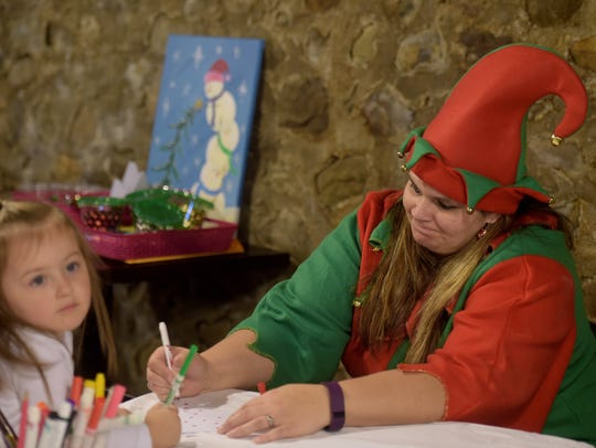 An elf helps color at Every Day Is Christmas/Sidewalk