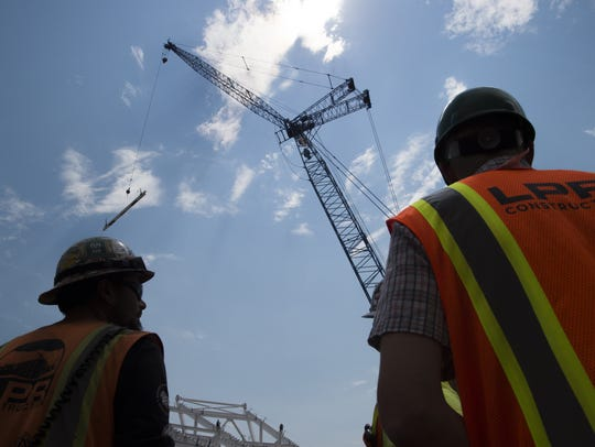 People gather to watch the last beam fall into place