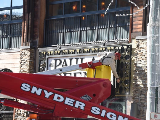 A worker pressure washes the sign for the Paula Deen