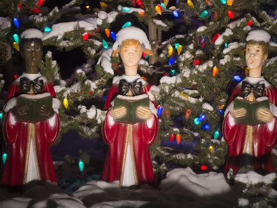 Figures of Christmas carolers stand covered in snow in the Woodward holiday display at the company's Drake Road campus. Company officials say they have no plans to eliminate the popular annual display.