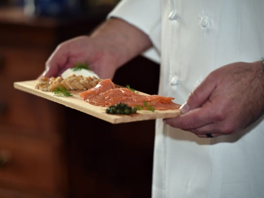 Chef David Raines carries a plate of smoked trout and salmon. Raines met his future wife while working in Copehnahgen, Denmark, where her restaurant had a pickled herring buffet.