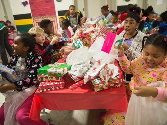 """Members of the fourth grade class gleefully open presents at David Hicks Elementary School in Inkster on Friday, Dec. 23, 2016 during a school party called """"The Miracle on Helen Street."""" Principal Amy Gee surprised the school with a decorated cafeteria and gifts to all her pupils."""