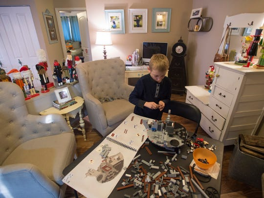 Parker Hobbs works on the Lego Death Star he was rewarded with after completing three years of cancer treatment at his home in Wellington Thursday, Dec. 22, 2016. The 10-year-old had his last treatment for leukemia this week.