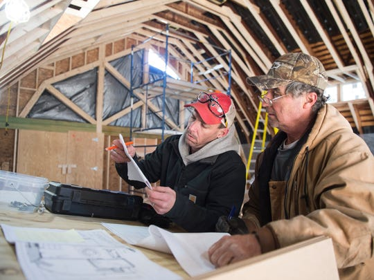 Jeremy Tibbs, left, and Mike Quinn look over building prints at a job site in Hanover on Wednesday, Jan. 4, 2017.