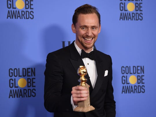 Tom Hiddleston poses with his Golden Globe for best actor in a miniseries or TV movie.