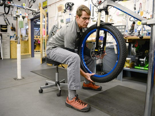 Bike technician David Abernethy spins the tire on a bicycle as he works to fix it in the shop at REI on Friday, Jan. 27, 2017.