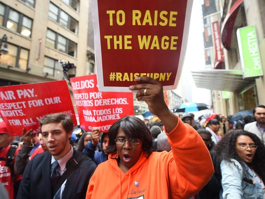 Fast food workers hold placards in support of increasing the minimum wage for such employees in New York.