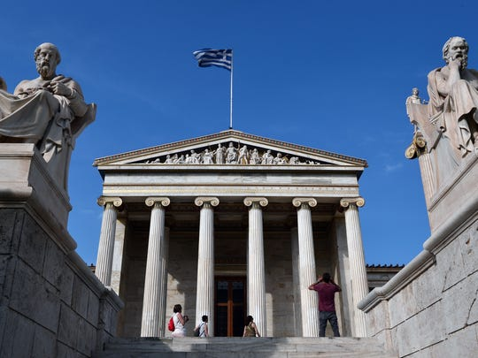 Tourists take pictures in front of the Athens Academy adorned with sculputures depicting ancient greek philosophers , Plato (L) and Sokrates (R) on June 10, 2016.