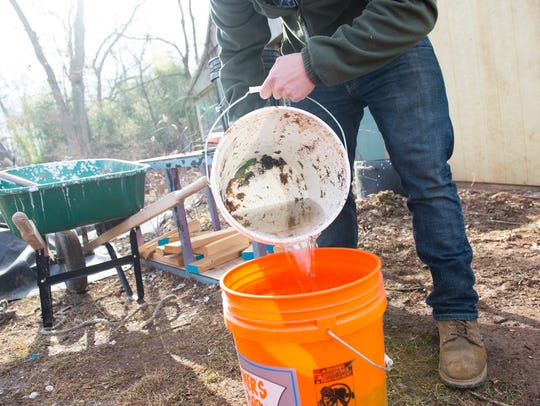 Tony Campisi pours rainwater into a bucket of compost