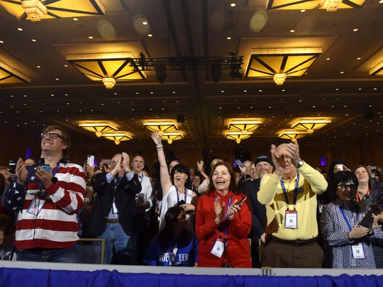 People cheer as President Trump addresses the Conservative