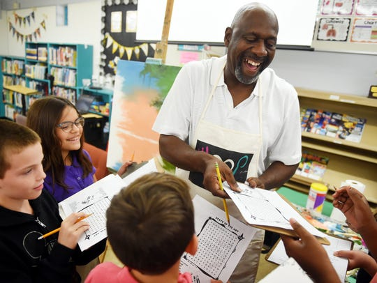 Vero Beach painter Ray McLendon shares a laugh with fifth-grade students Thursday, March 2, 2017, at Beachland Elementary School as he signs autographs after giving a talk about Florida Highwaymen art.