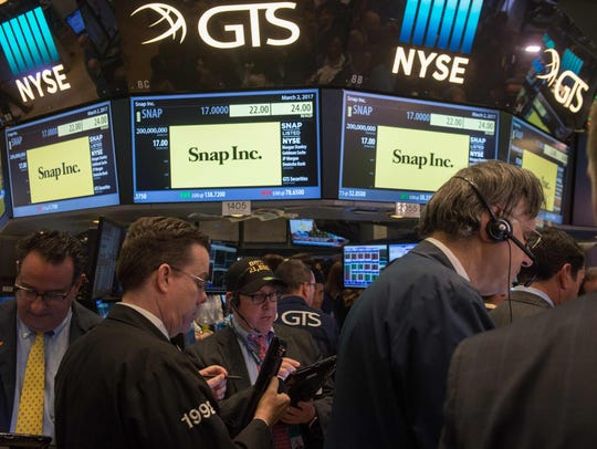 Traders work on the floor during the Snap Inc. IPO