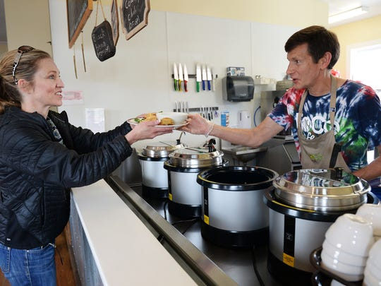 Co-Founder Jeff Baumgardner hands a plate to Kelly Giddens at FoCo Cafe on Tuesday, April 19, 2016. The nonprofit restaurant runs on volunteer labor and serves meals on a donation basis.