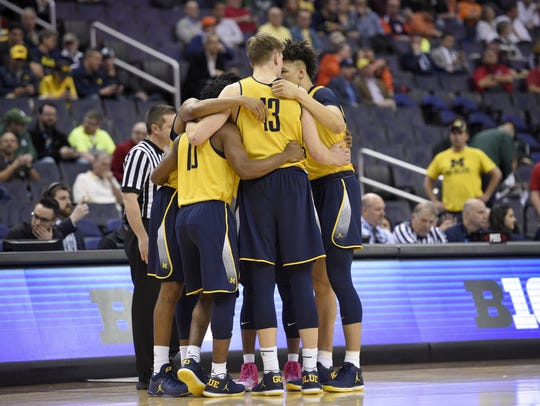 Michigan forward Moritz Wagner (13) and others huddle