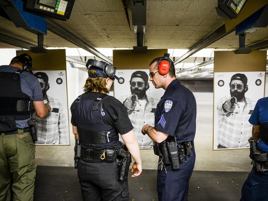 Fort Collins Police Officer Brett Dollar, center left, speaks with Jerrod Kinsman during a training day at the department's shooting range on Feb. 18, 2015. Fort Collins and Loveland have revived the proposal to build a shared training campus.