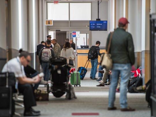 People wait to board Delta flight Delta 7435 to Detroit