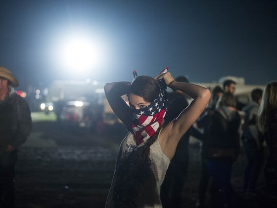 Sarah Minker, 26, ties an American flag bandanna around her face during the Country Thunder music festival in Florence on Monday, April 10, 2017.