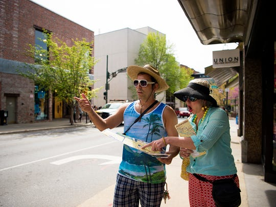 LaZoom owners Jen and Jim Lauzon, acting as lost tourists for a photo shoot, look at a map of Asheville on Haywood Street in downtown.