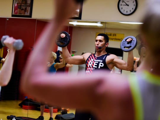 """Teddy Cravens leads a fitness class at the York JCC before cleaning up and heading to the salon where he works as a master stylist. """"I'm blessed that both of my occupations, they don't really feel like work,"""" Cravens said."""