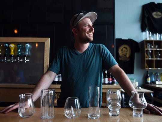 Matthew Cummings, owner of Pretentious Glass and Beer Co., stands behind six of his glass creations in Old City.