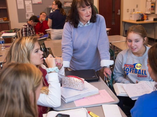 North High School pre-calculus teacher Jane Bernhardt, center, goes over a homework problem with a group of her students earlier this year.