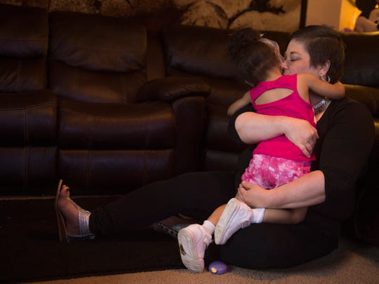 Heather Ota engulfs her youngest daughter, Kimiko, 3, in a hug before dinner Thursday evening. Heather is sure her older children will always remember her, but makes sure to make as many videos of herself as possible so the youngest will have something to remember her by.