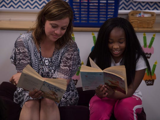 "Evansville Christian School third-grade teacher Beth Moore and Maliyah Woods take turns reading from ""Charlotte's Web"" during class recently."