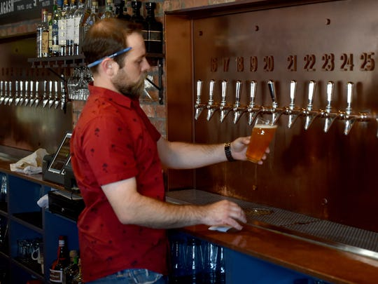 Jake Schumacher, General Manager at Finney's Crafthouse and Kitchen in Westlake, pours a beer from the fountain wall during a busy Monday afternoon.