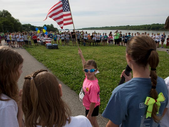 Elcie Arnold, 6, holds the American flag aloft for the Pledge of Allegiance that kicked off Newburgh Elementary School's Wildcat Mile at the Newburgh, Ind., Ohio River waterfront Monday morning.