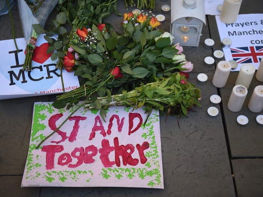 Candles , signs and floral tributes left at a vigil