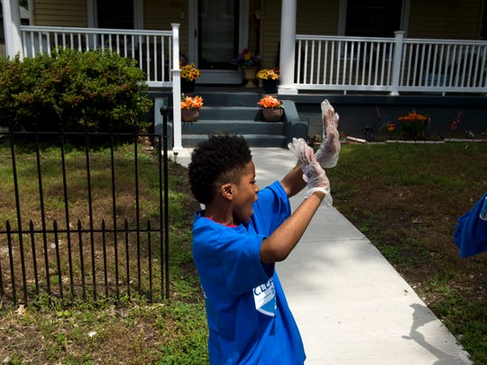 Marcus Johnson, 8, dances as he works at picking up