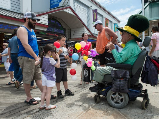 Children's entertainer, William Campion, right, talks with Anthony Marinella, of Gerrardstown, West Virginia and his two children Anthony Jr., 8, and Gianna, 6, on the Boardwalk in Ocean City on Saturday, May 27, 2017.
