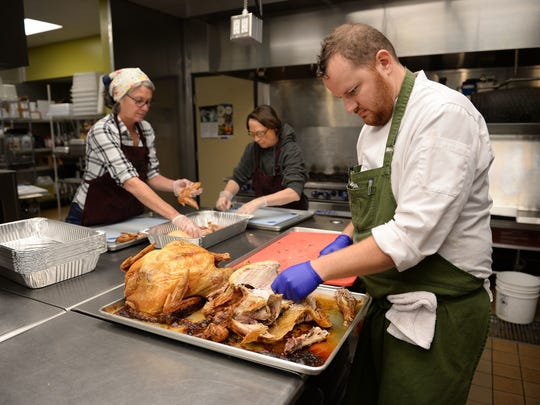 Community kitchen manager Justin Kruger prepares turkeys for the Matthews House's annual Thanksgiving dinner.