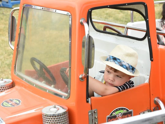Two-year-old Graham Keskitalo of Canton looks like he's in training for rush hour traffic as he wonders when the ride will start to move out.
