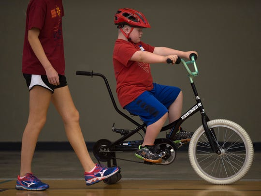Josh Groben, 10, of Evansville pedals along the gym floor at the National Guard Armory with Lydia Young, 16, close by during the iCan Bike camp Tuesday morning.