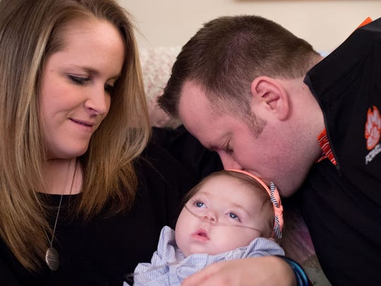 Powell girls basketball coach Christin Webb, her husband Kyle and their 10-month-old daughter Mabry Kate at their home on Wednesday, January 21, 2015. Mabry Kate was diagnosed with Krabbe disease six months after her birth. It is a degenerative condition that is fatal at around age two. The Webb's are fighting to pass legislation to test pregnancies for the disease, which can be often be treated successfully before symptoms of the disease begin to show.