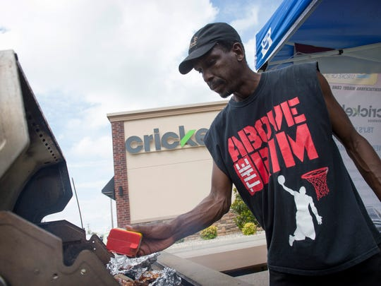 William Johnson of Henderson spices the meat on his grill at TBJ's outside Cricket Wireless at 2640 US Why 41N Friday afternoon. Both TBJ's and Cricket Wireless were donating three-percent of their earnings that day to the New Hope Animal Rescue Center.