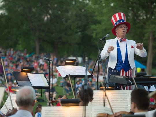 Fort Collins Symphony Musical Director Wes Kenney conducts a patriotic tune as Uncle Same to celebrate Fourth of July at City Park on Tuesday, July 4, 2017.