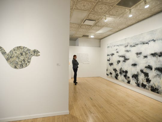 Volunteer Jen Ostler stands among the artwork featured