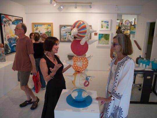 Artist Travis Blanton (left) talks about her ceramic