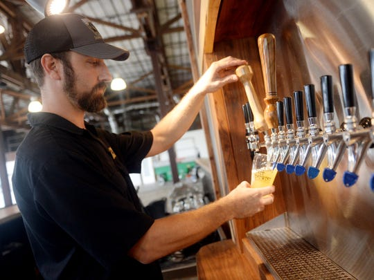 The Walking Tree Brewery will celebrate its first anniversary Saturday with a block party. Alan Dritenbas, co-founder of the Vero Beach brewery, pours a glass of Single Girlfriend, a Belgian-style beer with grapefruit, in 2016.