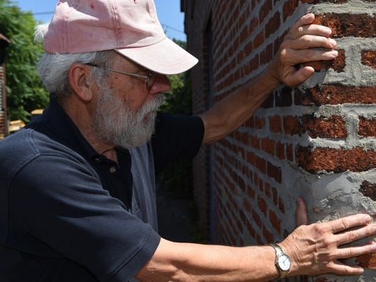 Roy Budnik, a geologist, Town of Poughkeepsie resident, and owner of 489 Main Street in the City of Poughkeepsie, is pictured with part of the original outer 1873 structure of the building.